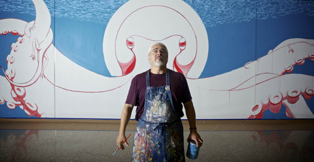 """Artist Kevin Obregon stands in front of his massive """"Oztopus"""" mural in the artist's wing"""