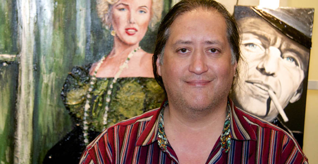 Artist Richard Nuñez stands before his Marilyn Monroe painting that was shot up.