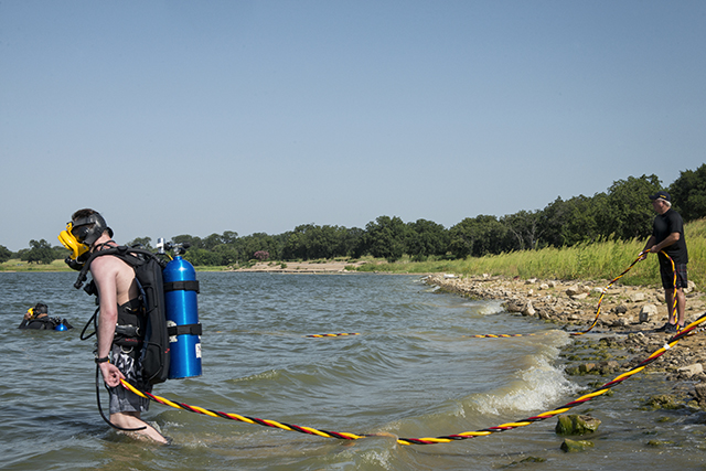 Above: Dallas police diver Daniel Hale enters the water at Lake Ray Hubbard. Below: Dive-team members test out new surface air-supply and communication equipment that  allows for more-effective underwater investigations.  Photo by Danny Fulgencio